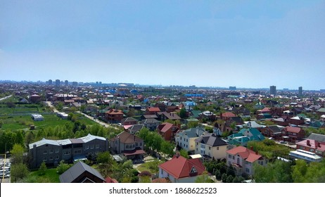 Panorama of a Krasnodar dormitory town from under the blue sky in spring. 				Spring in a southern dormitory suburb. 				Krasnodar outskirts on a sunny day. 				Tree-lined streets with houses of a bedroom suburb.