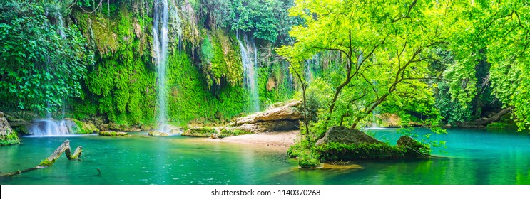 Panorama of Kursunlu waterfall with tiny islet, green precipice behind the falls, clear surface of the lake, Aksu, Turkey.