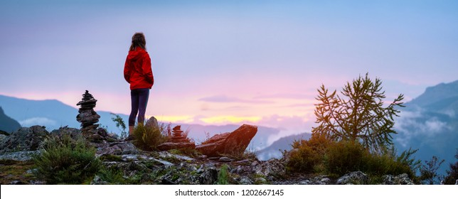 Panorama with lady hiker standing on top of the mountain among stacked stones and enjoying sunset over the valley. Altai, Russia