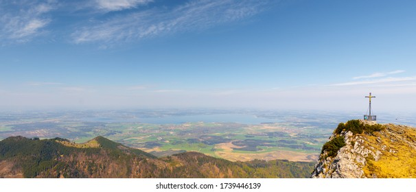 Panorama of Lake Chiemsee with summit cross of mountain Hochfelln