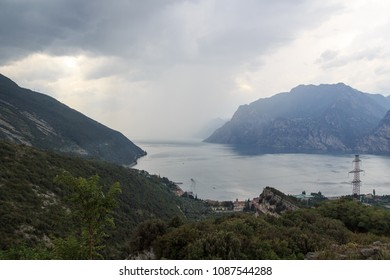 Panorama of Lake Garda and mountains with dark storm clouds, Italy