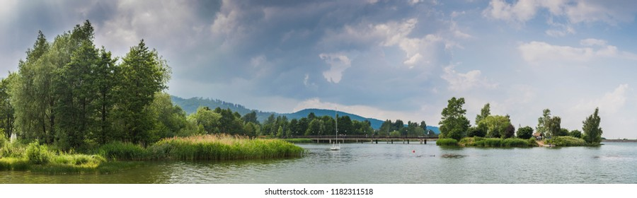 Panorama of lake, green trees and moutains with clouds. Bielawa, Zalew.