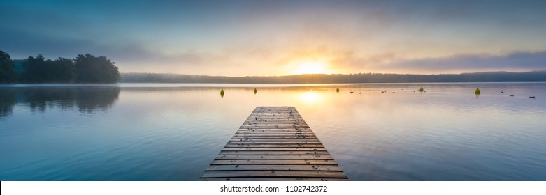 Panorama of a lake with a jetty at sunrise