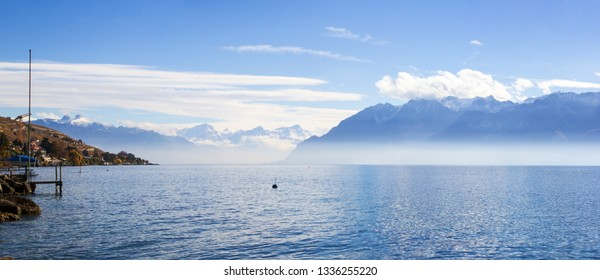 Panorama of Lake Leman or Lake of Geneva with morning mist over the water surface. At the background are the snow-covered Alps, at the right side is mountains in France. (large stitched file)