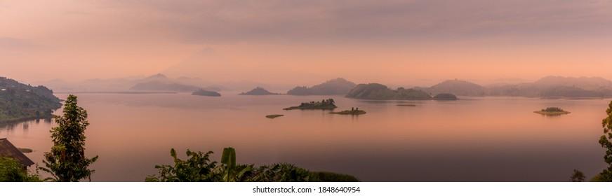 Panorama of Lake Mutanda at morning with view on the volcanoes mount Muhavuru and mount Gahinga in East Africa, along the border of Rwanda and Uganda.
