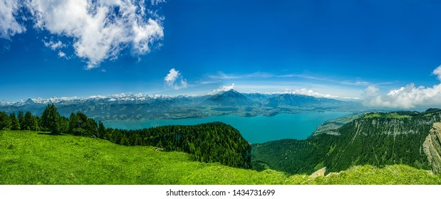 Panorama of Lake Thun and Bernese Alps including Jungfrau, Niesen, Eiger and Monch peaks from the top of Niederhorn in summer, Canton of Bern, Switzerland.