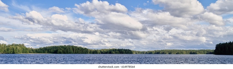Panorama lakeside landscape with dramatic cumulus clouds in the bright summer day scene in Finland.