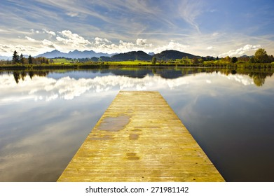 panorama landscape in Bavaria at alps mountains with lake and landing stage and mirroring