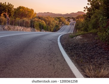 panorama landscape of beautiful amazing road with wonderful scenic view on Mallorca Majorca Spain taken at sunset sunrise dusk dawn with dreamy soft purple tones, clear sky and green trees and bushes