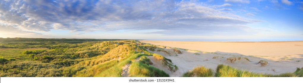 Panorama landscape coastline Dutch North Sea coast at IJmuiden during sunrise in warm clear light with low plain, dunes and wide beach with sea view against sky with scattered clouds