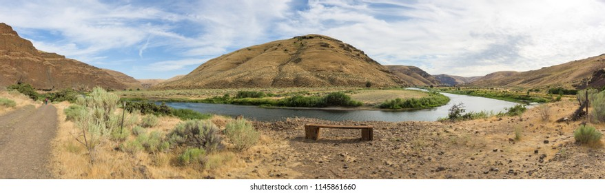 Panorama landscape of Cottowood Canyon State Park, Oregon, with mountains reflecting in a river and rock formations.