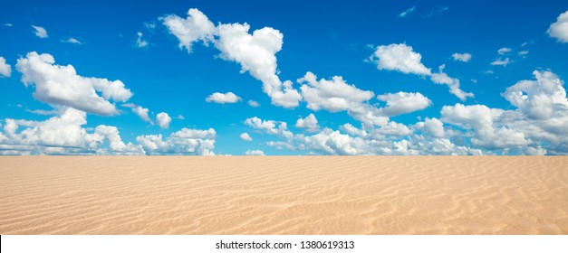 Panorama Landscape Of Desert And blue Sky clouds Background.Desert sand dunes landscapes on a bright sunny day with patterns formed in the sand by the wind.
