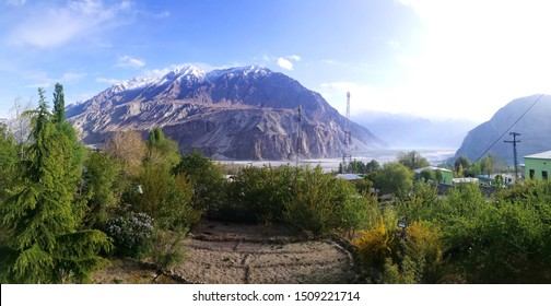 Panorama landscape of Khaplu village, Skardu, Pakistan with greenery blank farmland foreground, wide sand bank of Indus river and rock mountain valley in summer and sunny day