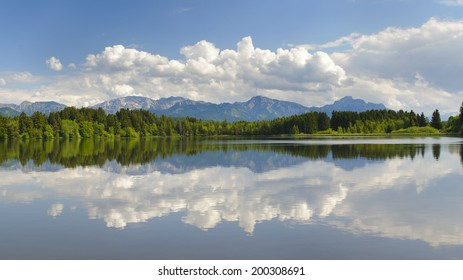 panorama landscape with lake Hopfensee and alps mountains in Bavaria