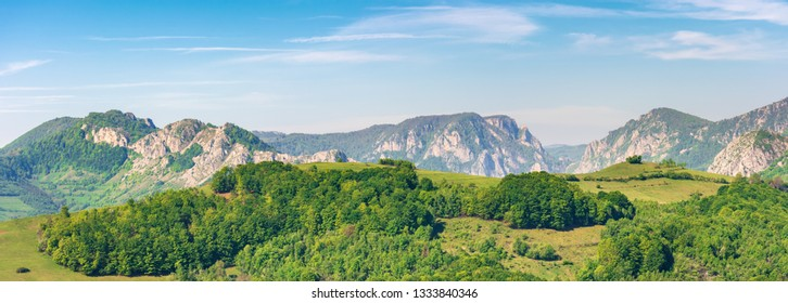 panorama of a landscape with rocky ridge. forested hill in front. wonderful springtime scenery. calm weather with blue sky