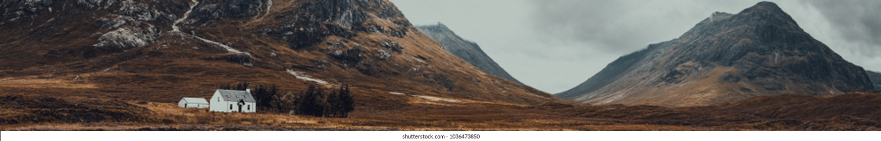 Panorama landscape view of Glencoe area with a white cottage and mountains in the plane of view