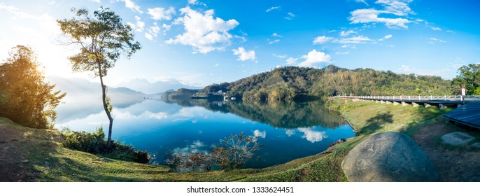 Panorama landscape of wooden bike trail beside lake and street under blue sky and white cloud at Sun Moon Lake with reflection, Nantou, Taipei