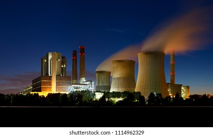 Panorama of a large brown coal power station with night blue sky and steam.