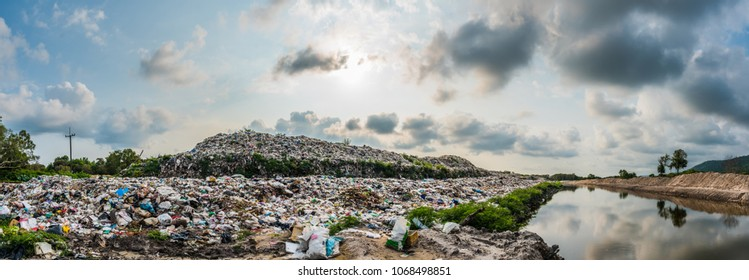 The panorama of large heap garbage dump extends parallel to the river,Garbage mountains with cloudy sky  back ground in day light,Waste has petroleum products are the major.
