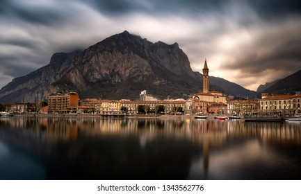 Panorama of Lecco city reflected on the lake in a amazing cloudy day, Lombardy, Italy