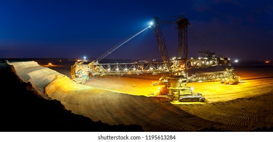 Panorama of a lignite surface mine with a giant bucket-wheel excavator, one of the worlds largest moving land vehicles with night blue sky.