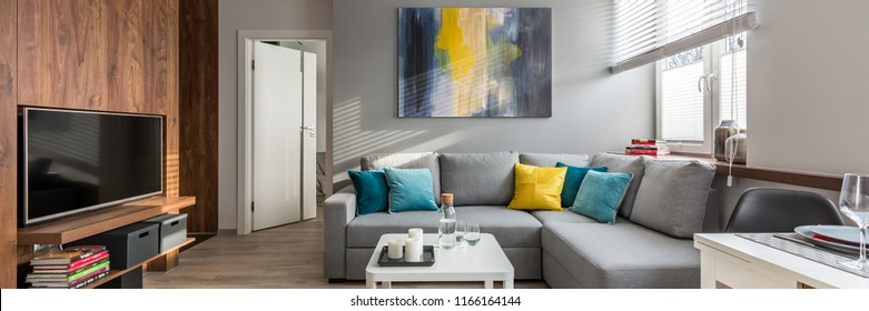 Panorama of living room with wooden wall and gray corner sofa