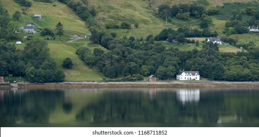 Panorama of Loch Broom, Inverness, Scotland. August 2018. White painted house on the shore of the loch, reflected in the water.