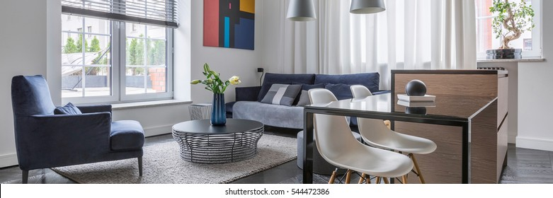 Panorama of loft interior with sofa, armchair, table and big window with blinds
