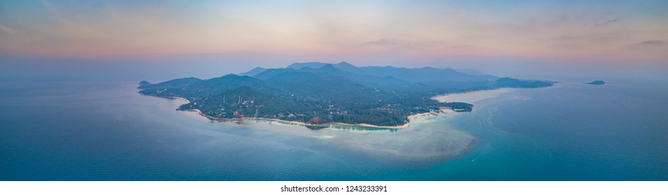 Panorama lone standing island. Sunset aerial drone shot. Ko Pha-ngan. Thailand. Overwhelmed view from above Ko Pha-ngan island and the ocean at the colorful sunset. The Kingdom of Thailand.