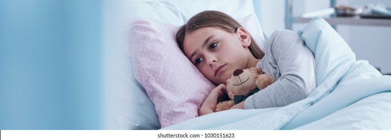 Panorama of lonely, sick girl hugging a plush toy in the hospital