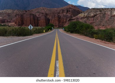 Panorama of a lonely street through the Quebrada de Humahuaca in Argentina with massive rocks in the background