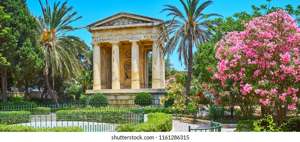 Panorama of Lower Barrakka Gardens with Neoclassical memorial, tall palm trees, blooming pink rhododendron and the fountain, Valletta, Malta.