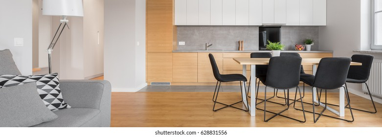 Panorama of luxury kitchen with big table and black chairs open to living room area