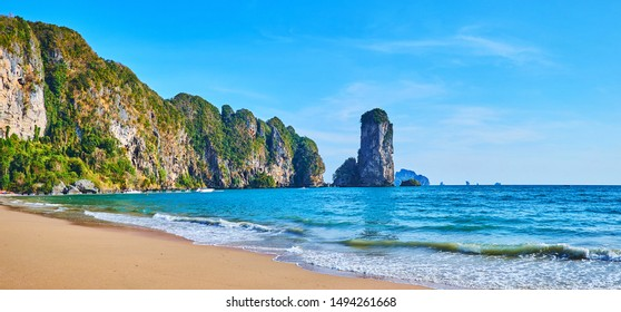 Panorama of the luxury sand Monkey beach, surrounded by tall rocky cliffs and lush tropical greenery, Ao Nang, Krabi, Thailand