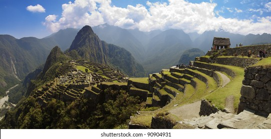 Panorama of Machu Picchu, Guard house, agriculture terraces, Wayna Picchu and surrounding mountains in the background.