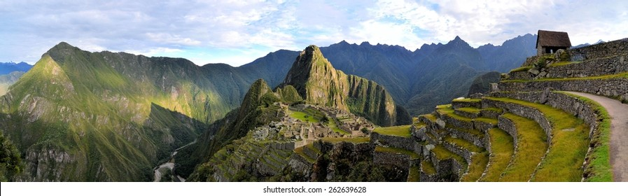 Panorama of Machu Picchu terraces, watcher's hut and Wuayna Picchu with shadow in early morning light. Machu Picchu is the famous lost city of the Incas near the river Urubamba located in the region