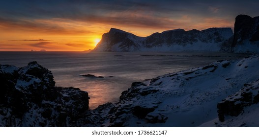 Panorama of Mahornet summit and Vaeroy ridge at orange sunset, Lofoten Norway