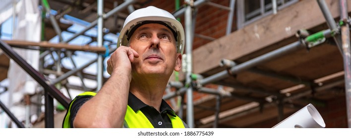 Panorama of male builder foreman, worker or architect on construction site holding building plans and talking on his cell phone panoramic web banner