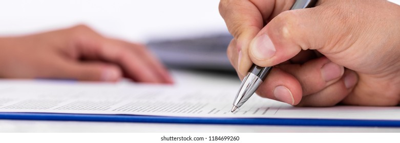 panorama of a man, signing a document on a blue clipboard, hand of a woman in the background