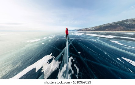 Panorama man stand on cracks on blue ice of Lake Baikal from Olkhon.
