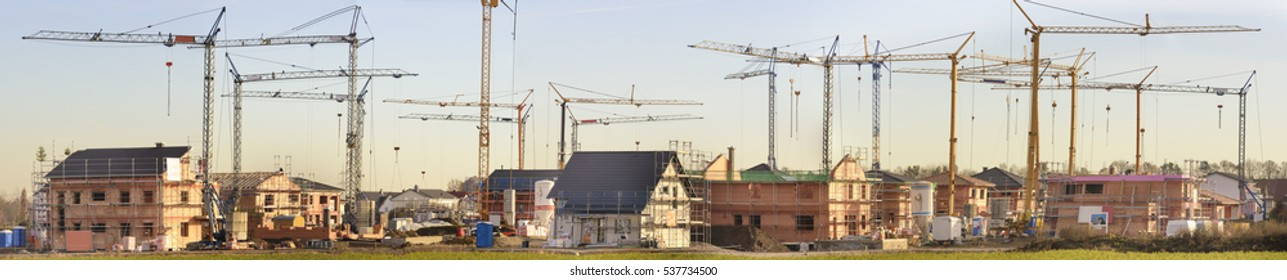 panorama of many residential houses under building construction with many cranes