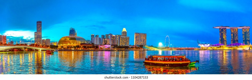 Panorama of marina bay skyline with evening lights reflecting in the sea at blue hour. Singapore cityscape by night. Night scene waterfront.