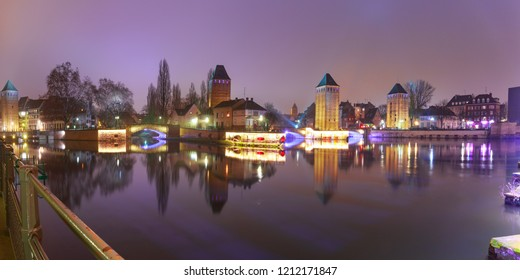 Panorama of medieval towers, bridges Ponts Couverts and Barrage Vauban with mirror reflections in Petite France during twilight blue hour, Strasbourg, Alsace, France