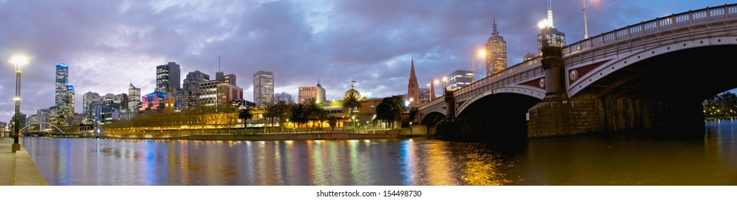 Panorama of Melbourne with city lights reflected in yarra river at dusk