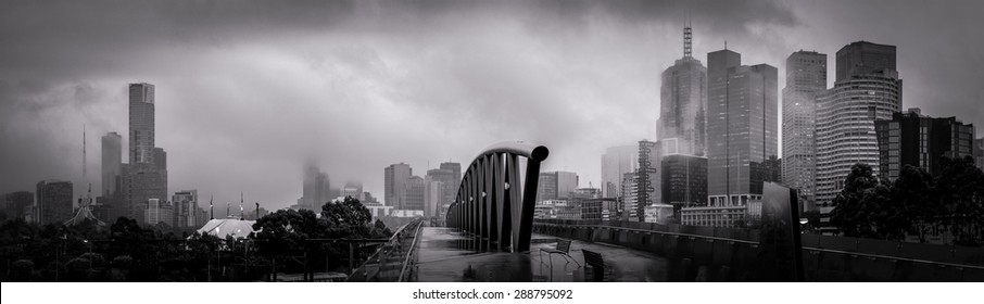 panorama of melbourne of a cold winter morning loking over a walk bridge towards the city centre with lots of clouds