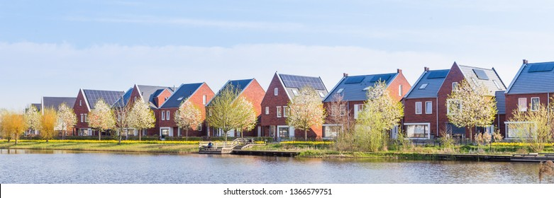 Panorama with modern brick houses along water in a family friendly suburban neighborhood in Veenendaal in the Netherlands.