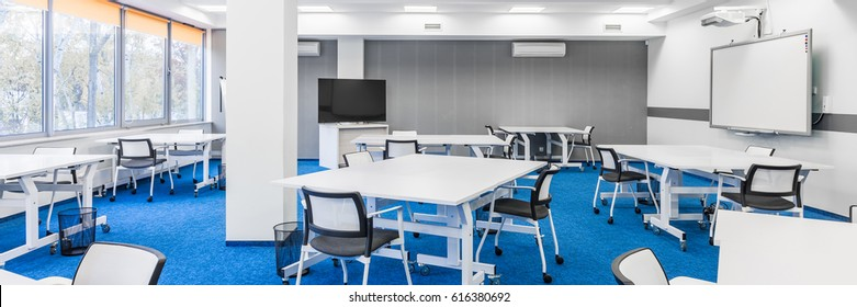 Panorama of modern college group study room with white desks, chairs, big tv screen and board