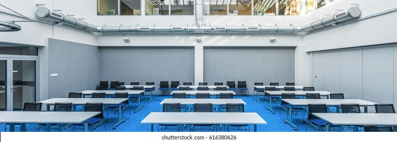 Panorama of modern college study hall in blue and grey with tables and desks