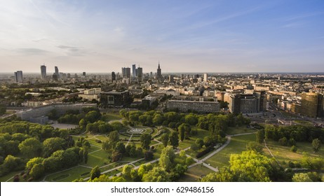 Panorama of a modern european city. Skyline of Warsaw, capitol of Poland. Green park and trees in foreground, urban city in background. Sunny weather.
