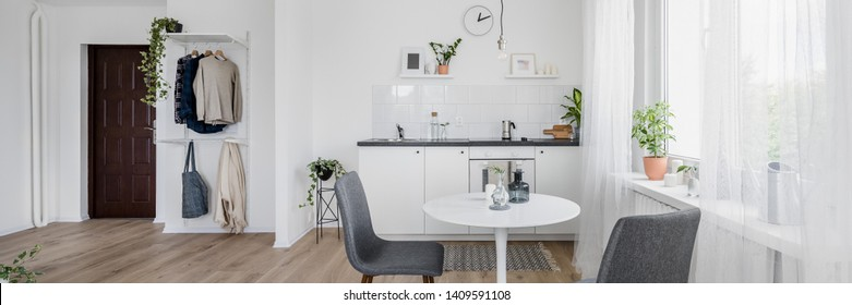 Panorama of modern kitchen interior with round dining table and two chairs